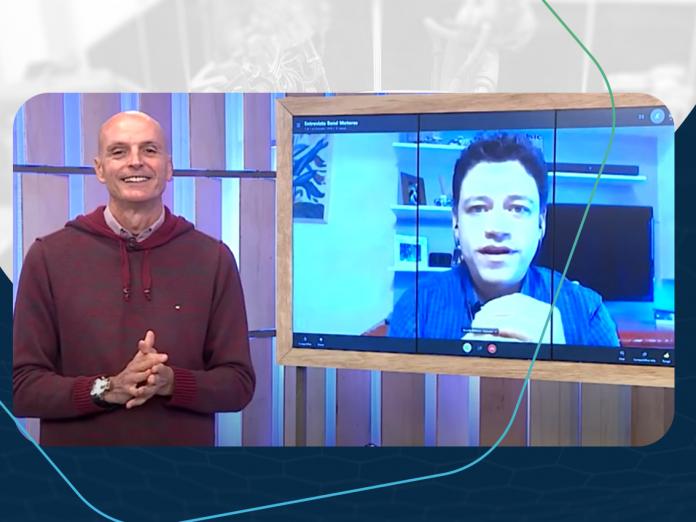 Ricardo Barbosa, gerente de produto Automec, em televisão de estúdio de TV conversando com apresentador do Band Motores