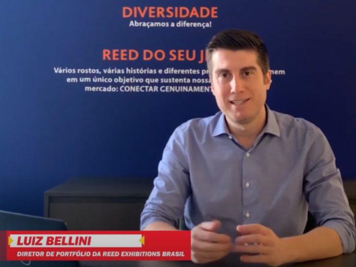 Luiz Bellini, diretor da Automec, fala em vídeo. Bellini é um homem branco, que veste camisa social azul e está sentado, com os antebraços apoiados em mesa, com fundo azul e algumas frases de cultura e valores da empresa Reed Exhibitions