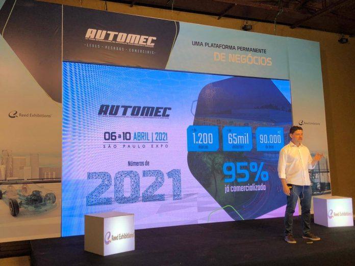 Ricardo Barbosa, vestido de camisa branca e calça jeans, aparece à esquerda de painel ao fundo que mostra números da Automec, em tons de azul claro, azul escuro e branco, com a logomarca Automec escrita no topo.