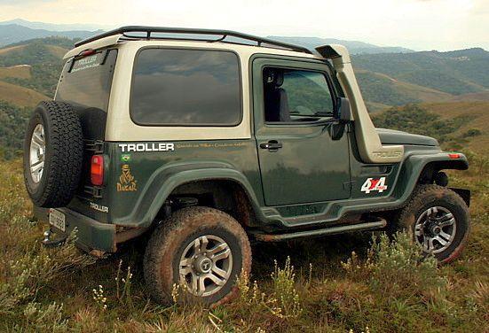 Carro Troller a partir de visão da lateral direita, estacionado em gramado no alto de planalto